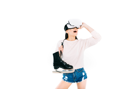 surprised asian girl in virtual reality headset holding skates isolated on white