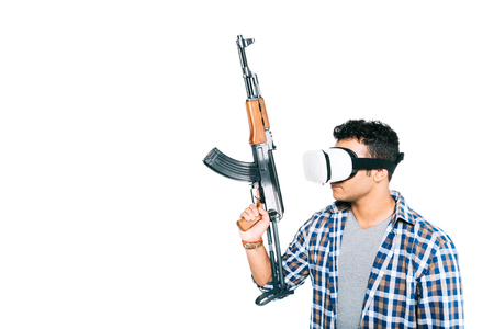 young man in checkered shirt and virtual reality headset holding rifle isolated on white