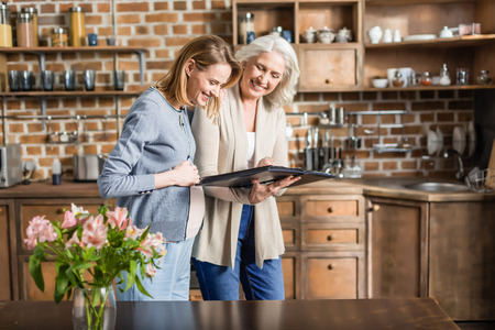 Portrait of young pregnant woman and her senior mother looking at photo album at table in kitchen