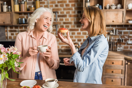 Portrait of two women, senior and young eating strawberry tart during their lunch Reklamní fotografie