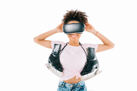 smiling african american girl with skates around neck adjusting virtual reality headset isolated on white Stock Photo