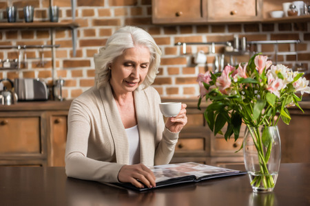 Portrait of senior gray hair woman sitting at kitchen table and looking at photo album