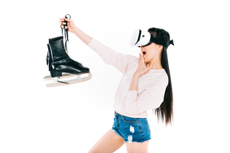 surprised asian girl in virtual reality headset holding skates isolated on white  Stock Photo