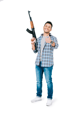 smiling young african american man holding rifle and showing thumb up isolated on white