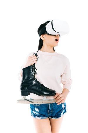 shocked asian girl in virtual reality headset holding skates isolated on white   Stock Photo
