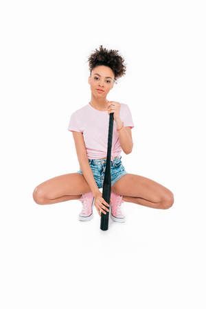 attractive young african american woman crouching with baseball bat isolated on white