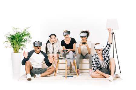 multiethnic group of happy young friends in virtual reality headsets playing video games together