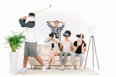 emotional young multiethnic people in virtual reality headsets looking at friend playing golf isolated on white