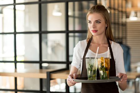 portrait of young waitress in apron holding tray with refreshing drinks in cafe Foto de archivo