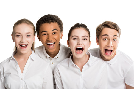 portrait of screaming multiethnic teenagers in white shirts isolated on white