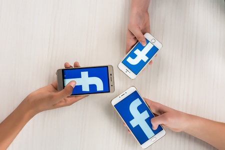 cropped shot of teenagers holding smartphones with facebook logo on screens in hands Sajtókép