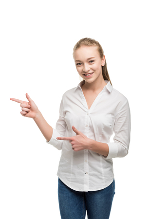 portrait of smiling caucasian teenage girl pointing away and looking at camera isolated on white