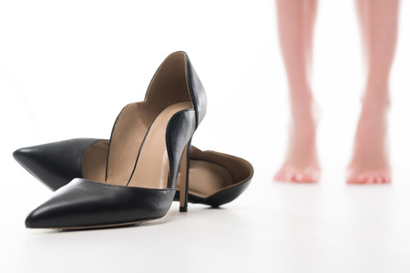 cropped view of tired female legs and heels, isolated on white 写真素材