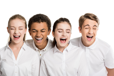 portrait of screaming multiethnic teenagers with closed eyes in white shirts isolated on white