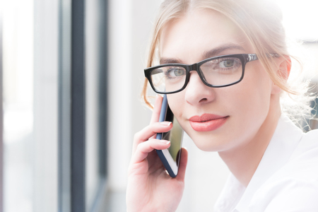 beautiful businesswoman in eyeglasses using smartphone in modern office