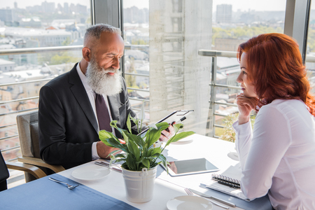 handsome mature businessman looking at contract given from female partner