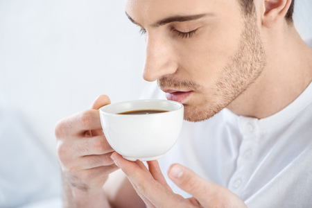 young handsome man with closed eyes drinking coffee