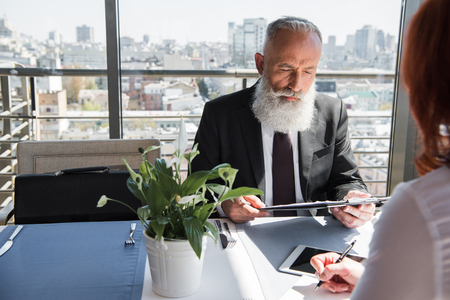 concentrated mature businessman looking at contract given from female partner
