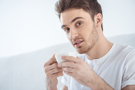 young handsome man drinking coffee in bed