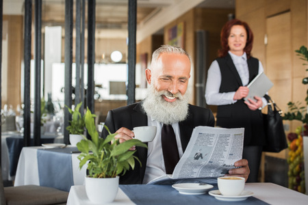 happy businessman reading newspaper in restaurant while waiting for meeting