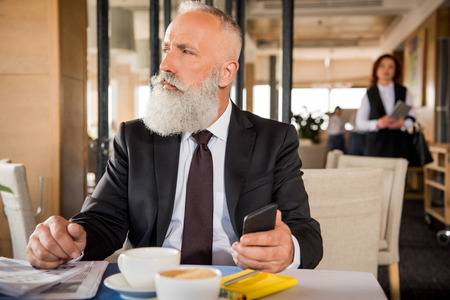 serious mature businessman using smartphone in restaurant while waiting for meeting Imagens