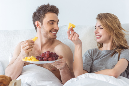 young happy couple with healthy breakfast in bed