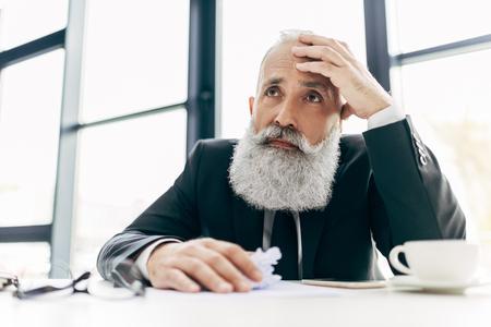 thoughtful senior businessman with massive grey beard at worplace Reklamní fotografie