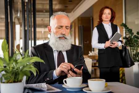 mature businessman using smartphone in restaurant while waiting for meeting