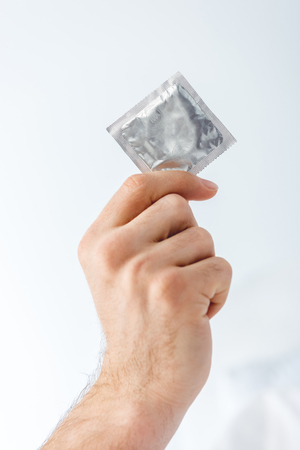 cropped view of man holding condom in hand isolated on white