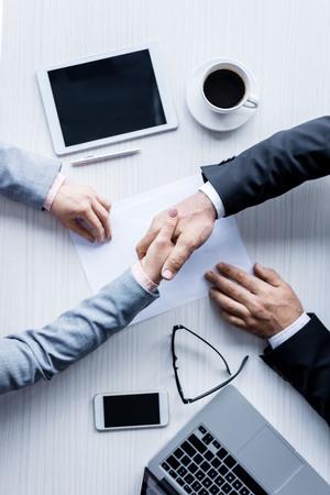 vue de dessus des gens d & # 39; affaires se serrant la main lors de la réunion