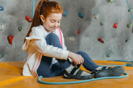 Little girl sitting on a mat in the gym and looking down, with climbing wall in the background