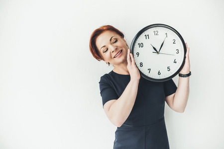 happy mature woman holding clock on white wall background
