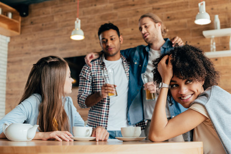 two drunk men are wary of young women sitting in cafe Stock Photo - 102622791
