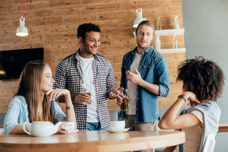 two men are wary of young women sitting in cafe Stock Photo