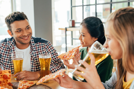 Group of young multiethnic friends having pizza in cafe Banque d'images - 102623022