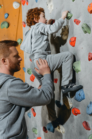 Little boy in a harness climbing a wall with grips at gym with his father securing him from the ground Stock Photo
