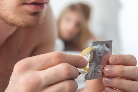 cropped view of man opening condom while his girlfriend lying behind in bed