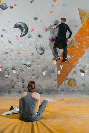 Full-length shot of a young man in sportive attire climbing wall with grips and woman sitting on mat watching him