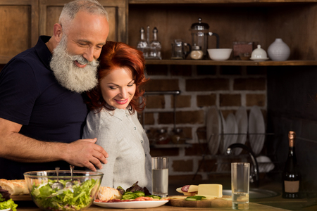 portrait of smiling senior couple looking at ingredients for dinner on table in kitchen