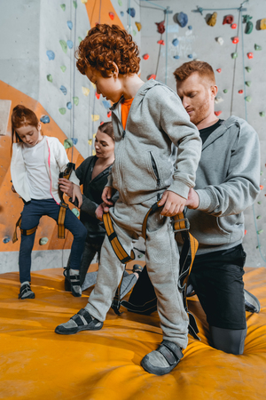 Full-length shot of young dad securing little son in a harness for climbing a wall at gym 스톡 콘텐츠 - 102625530