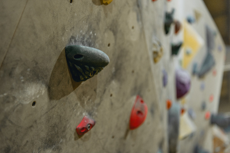 Closeup shot of grips for hands on a climbing wall at gym
