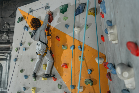 Full-length shot of little boy in a harness climbing a wall with grips at gym
