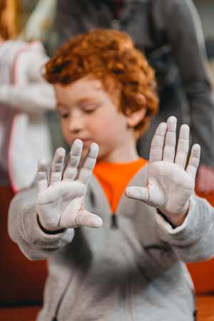 Closeup shot of a little boy in sportive attire showing his hands covered in talcum powder
