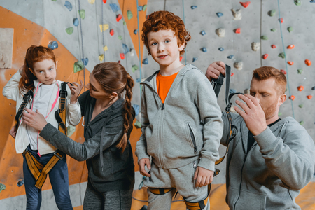 Half-length shot of parents securing their children in harnesses for climbing a wall with grips at gym Standard-Bild - 102639574