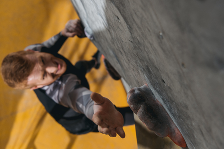 High-angle shot of young man in sportive attire climbing a wall with grips at gym  Stock Photo