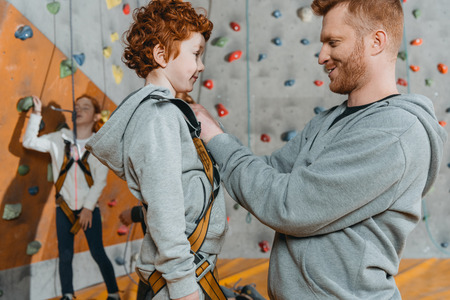 Side view shot of young dad securing little son in a harness for climbing a wall at gym