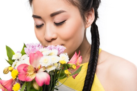beautiful asian girl with closed eyes smelling flowers isolated on white Stockfoto