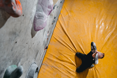HIgh-angle shot of a man sitting on mat near a climbing wall, covering his face with hands in defeat