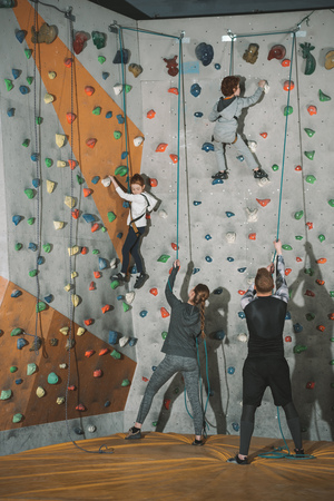 Full-length shot of two little kids climbing a wall at gym and their mother and father holding securing ropes