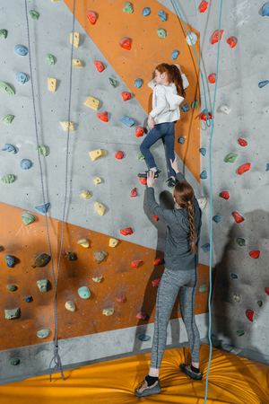 Full-length shot of little girl climbing a wall with grips and her mom supporting her from the ground
